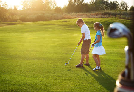 golf clubs: Casual kids at a golf field holding golf clubs. Sunset