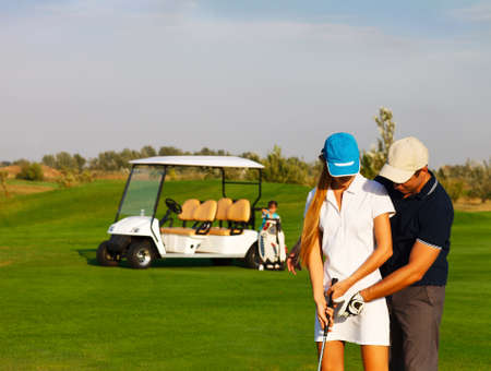 Young sportive couple playing golf on a golf course photo