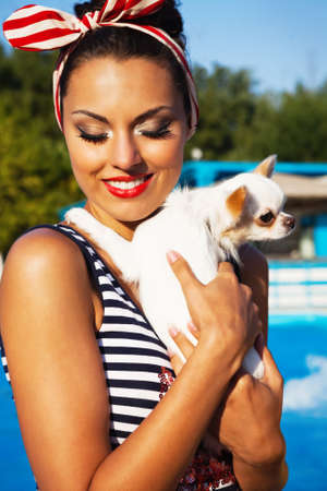 Beautiful pin up girl with puppy near the swimming pool. Summertime photo