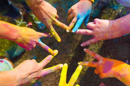 with friends: Amigos que ponen las manos juntas en se�al de unidad y trabajo en equipo. Festival de colores Holi. Concepto de la amistad