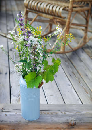 adirondack chair: Bright yellow and blue bucket with flowers on porch near the Adirondack rocking chair Stock Photo