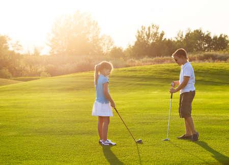 Casual kinderen op een golf veld bedrijf golfclubs. Zonsondergang Stockfoto