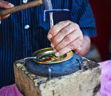 forgeman: Mans hands decorating golden plate with narrow focus