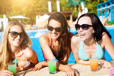 zomers drankje: Gelukkig meisjes met dranken op zomer feest in de buurt van het zwembad Stockfoto