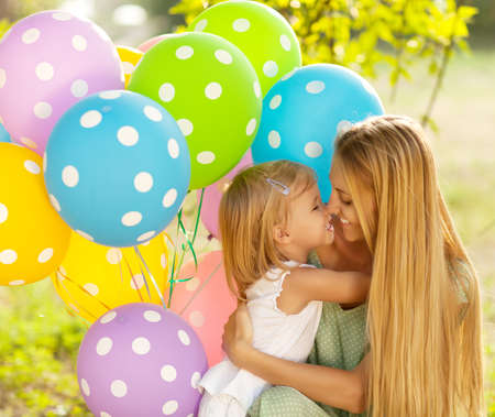 ballons: Happy woman and her little daughters with ballons outdoors. Mother day or Birthday concept Stock Photo