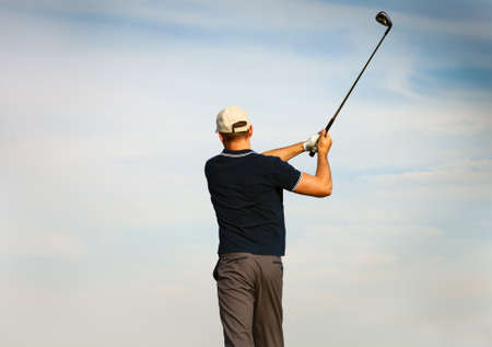 golf man: Athletic young man playing golf, golfer hitting fairway shot, swinging club