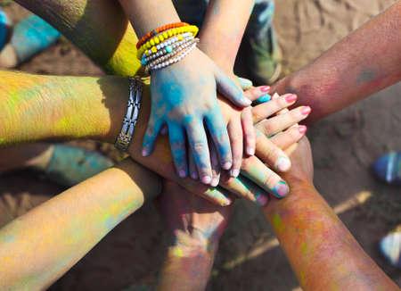 Freunde, die ihre Hände zusammen in ein Zeichen der Einheit und Teamwork. Holi Festival Farben. Freundschaft Konzept