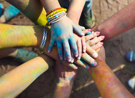 Friends putting their hands together in a sign of unity and teamwork. Holi colors festival. Friendship concept