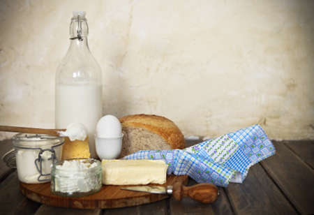 Bottle of milk, egg, butter, cream, bred, cheese and  cottage cheese on the wooden table. Close up photo