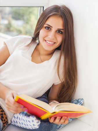 one room school house: Beautiful teen girl reading a book while sitting at a window Stock Photo