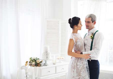 bodas de plata: Alegre casada pareja de pie en la sala blanca