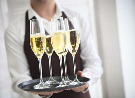 party tray: Professional male waiter in uniform serving champagne. DOF. Natural light. Photo in motion Stock Photo