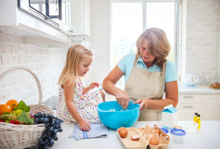 grandmother and children: Cute little girl baking with her grandmother at home