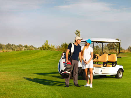 Young sportive couple playing golf on a golf course. Standing near the golfcar photo