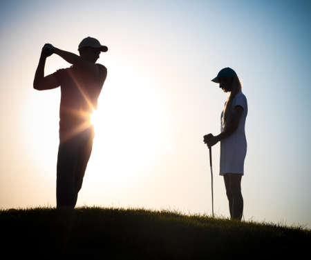 golf swing: Male and female golfers playing golf at sunset