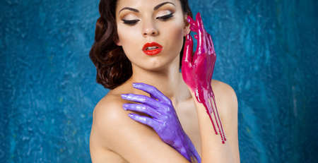 black hair blue eyes: Portrait of a beautiful young woman with bright make up and colored splashes hands Stock Photo