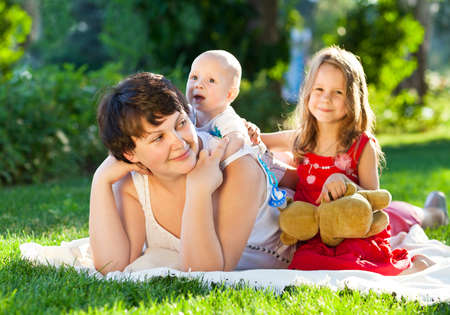 mom kiss son: Mother And her kids outdoors. Happy mum and her children playing in park together. Outdoor portrait of happy family