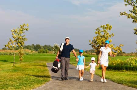 Familie der Golfer zu Fuß auf dem Golfplatz