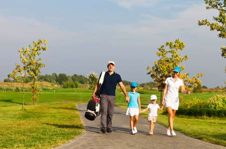 woman golf: Family of golf players walking at the course