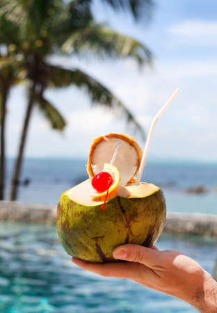 pool bar: Man holding coconut cocktail with drinking straw and cocktail cherry by the swimming pool