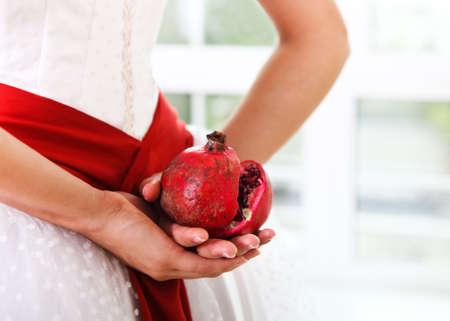 pomegranat: Pomegranat in hands of a bride. Close up