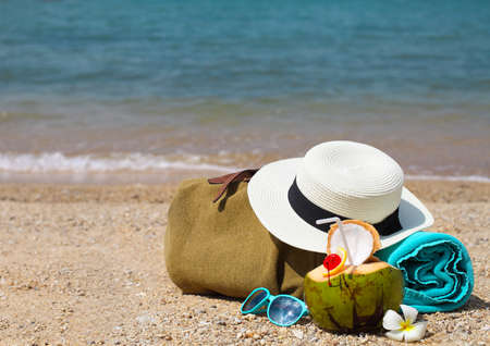 towel beach: Straw hat, sunglasses, beach towel with beach bag and coconut cocktail. Summer travel and vacation concept