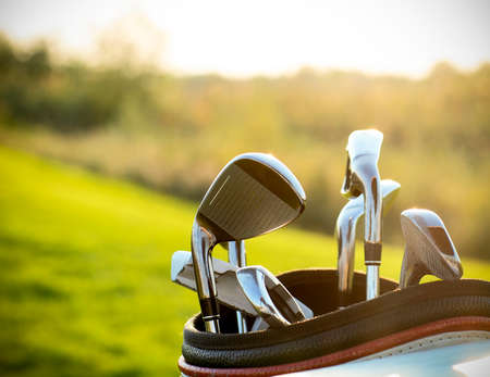 Golf clubs drivers over green field background. Summer sunset Stockfoto