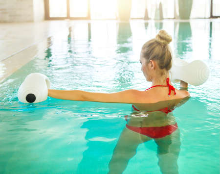 leisure centre: Blond young woman doing aqua aerobics with foam dumbbells in swimming pool at the leisure centre Stock Photo