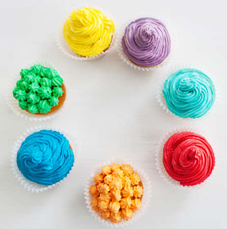 Rainbow Happy Birthday cupcakes on the white background with copy space photo