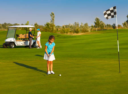 country club: Young sportive family playing golf on a golf course Stock Photo