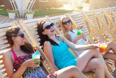 beach resort: Muchachas felices con las bebidas en fiesta del verano cerca de la piscina