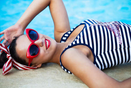 Beautiful pin up girl near the swimming pool. Summertime photo