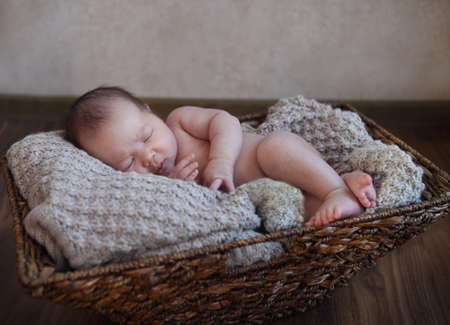 One month old baby boy in the basket on the wooden floor photo