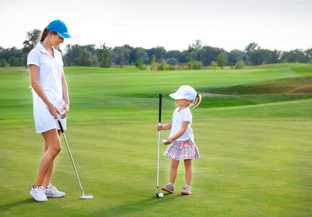 Mother and her little daughter practicing to hit the ball at the course 스톡 콘텐츠