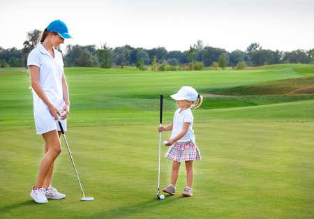 mutter und kind: Mutter und ihre kleine Tochter zu �ben, den Ball auf dem Golfplatz treffen Lizenzfreie Bilder