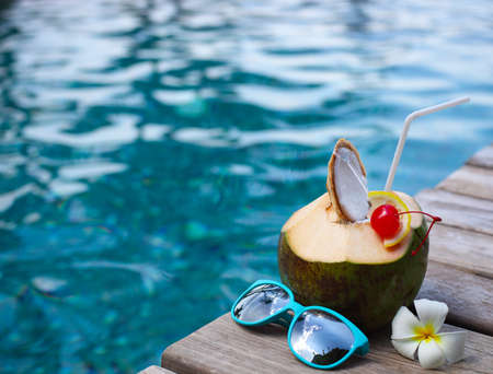 Coconut cocktail with drinking straw by the swimming pool with the sunglasses