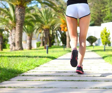 ccloseup: Runner feet running on road in the park. cCloseup on shoes. Woman fitness sunrise jog workout welness concept