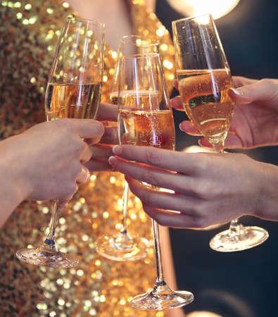 お祝い。シャンパン乾杯のグラスを持っている人。被写し界深度。自然光。モーションの写真。トーンのイメージ