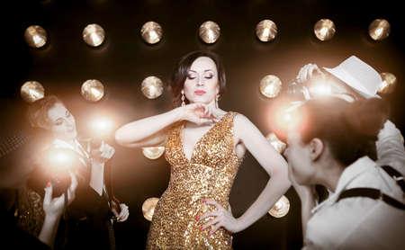 paparazzi: Superstar woman wearing golden shining dress posing to paparazzi