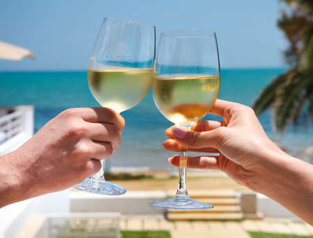 Man and woman clanging wine glasses with white wine at sky and sea background Stock Photo
