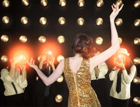 Superstar-Frau mit goldenen glänzenden Kleid posiert auf Paparazzi