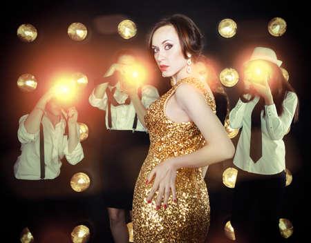 superstar: Superstar woman wearing golden shining dress posing to paparazzi