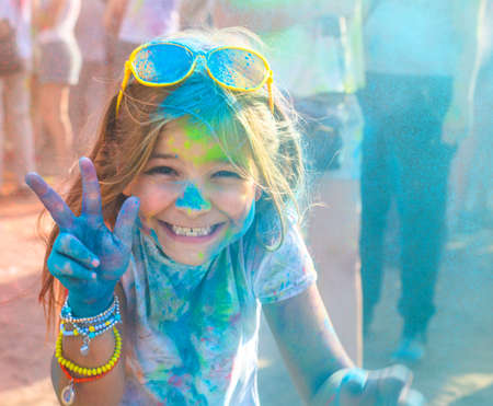 Portrait de jolie fille heureuse sur litttle festival de couleurs de Holi