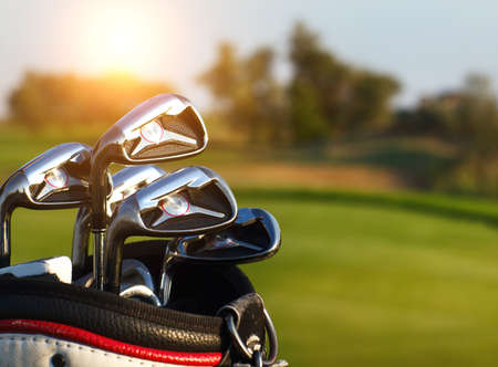 Golf clubs drivers over green field background. Summer sunset Archivio Fotografico