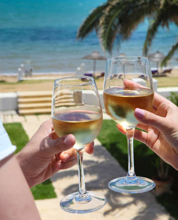 champers: Man and woman clanging wine glasses with white wine at sky and sea background Stock Photo