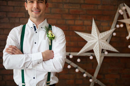 buttonhole: Groom wearing buttonhole with white anemone and fur tree
