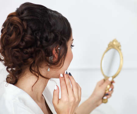 mirror face: Gentle young bride looks in the mirror. Bridal morning Stock Photo