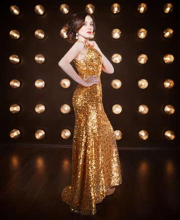 Superstar woman wearing golden shining dress posing Stock Photo
