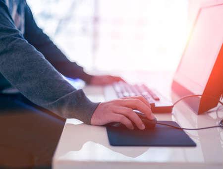 trabajando en computadora: Mano masculina que sostiene el rat�n del ordenador con el teclado del ordenador port�til en el fondo Foto de archivo