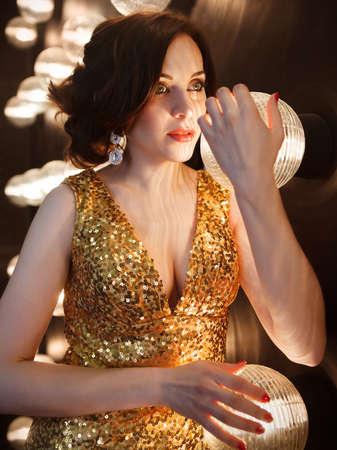 superstar: Superstar woman wearing golden shining dress posing Stock Photo